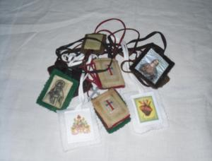 Several different kinds of scapular with their cords tangled.