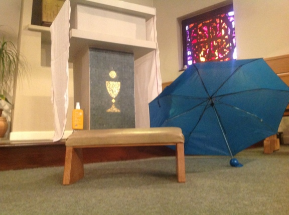 Umbrella, sun tan lotion, and prayer stool