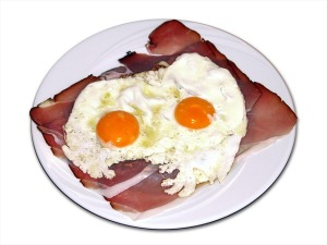 two fried eggs on a slab of bacon, on a white plate