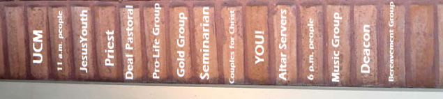 A row of vertical bricks with the names of parish activities on them