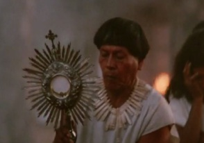 A South American native holds aloft a monstrance with the Blessed Sacrament