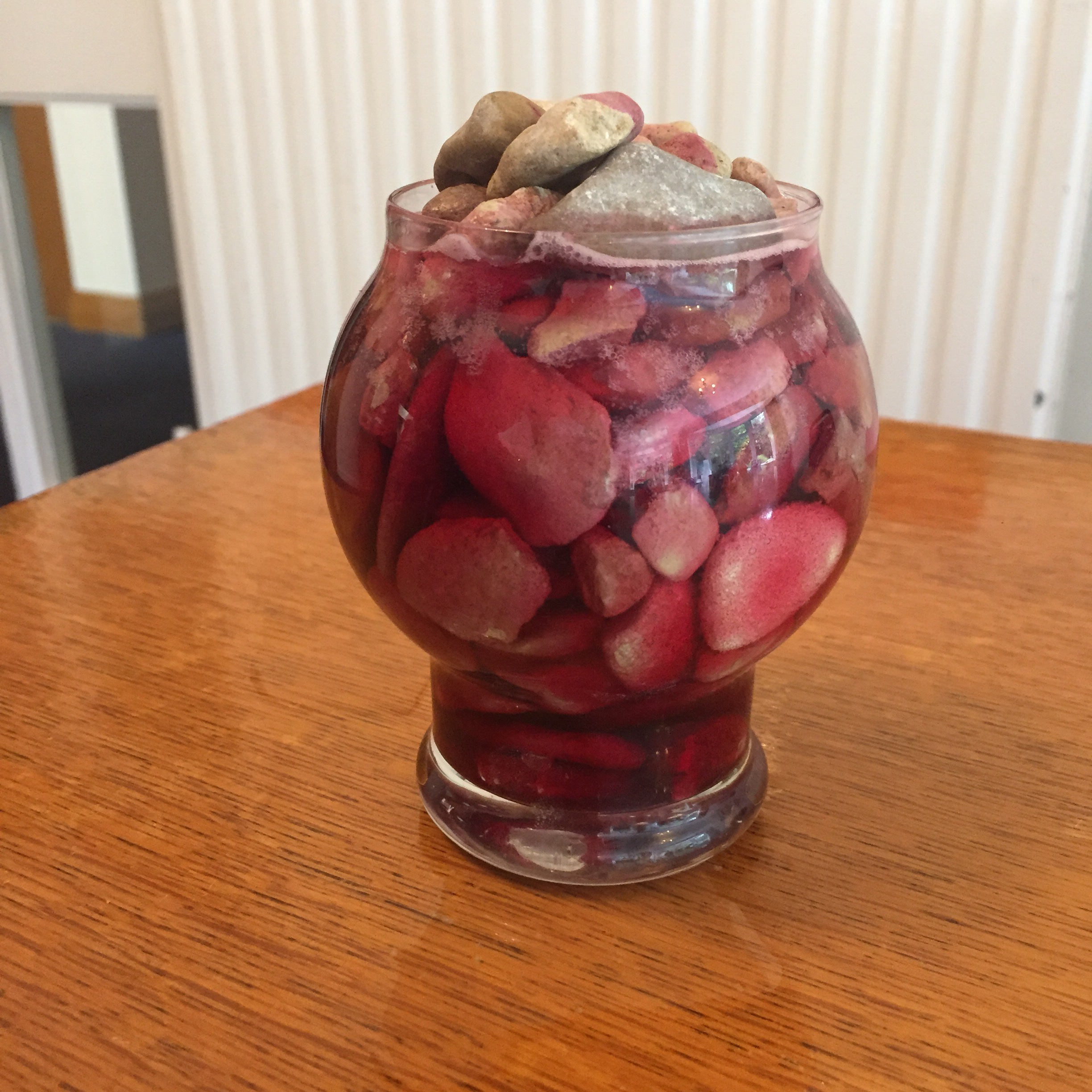 Stones in a vase filled with red liquid